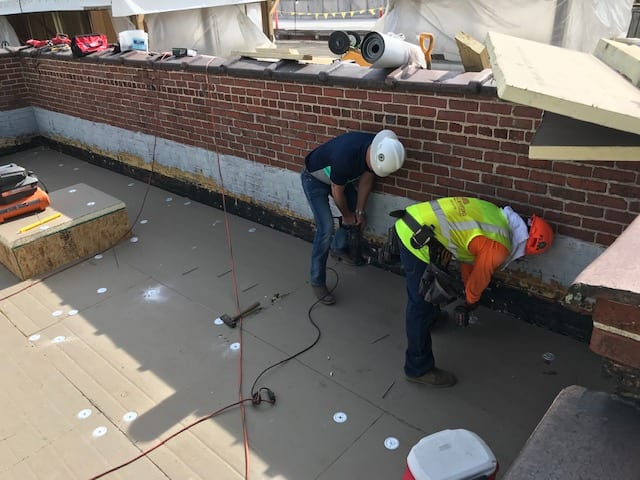 Two WNC Roofing team members working together to mechanically fasten membrane