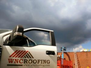 WNC Roofing logo Ford Truck door open with ladder to roof in Greenville SC