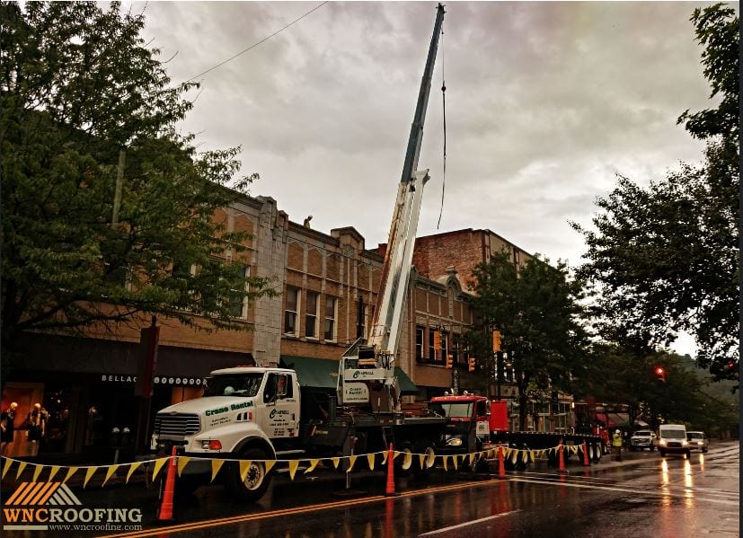Barleys Taproom in downtown Asheville with crane loading materials on roof