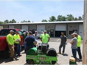 WNC Roofing team gathered around a glue cart for training