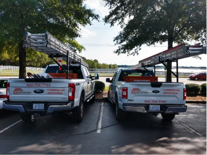 Two WNC Roofing Ford Trucks parked on site for roof repairs