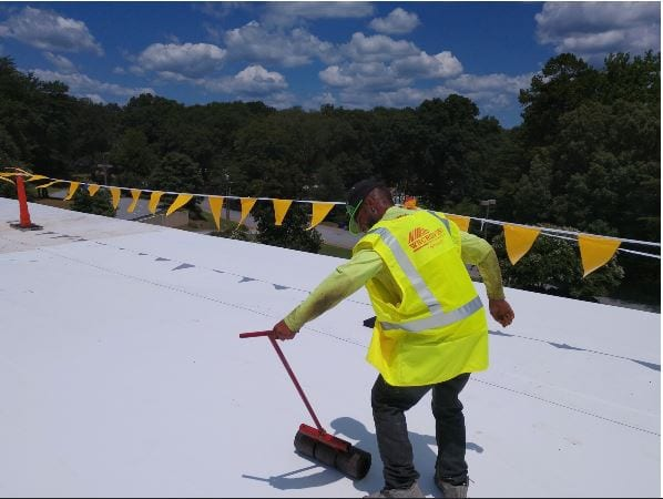 WNC Roofing crew member using a roller to smooth out white TPO Membrane