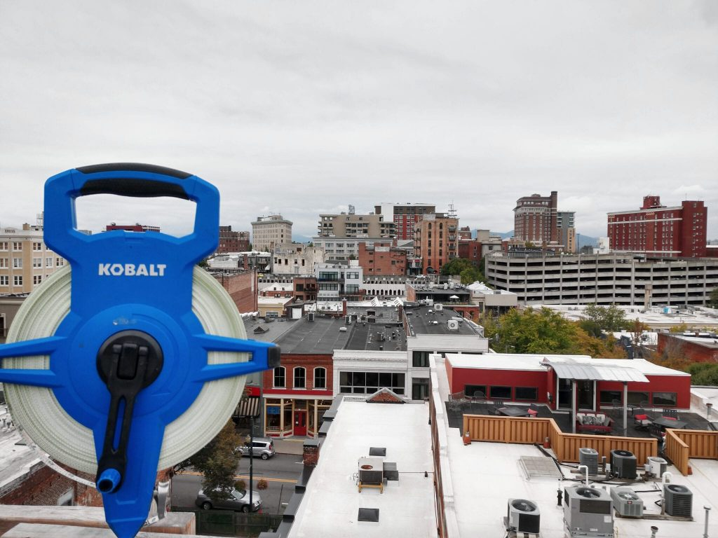 A tape measure and rooftop overlook in busy Downtown Asheville, North Carolina.