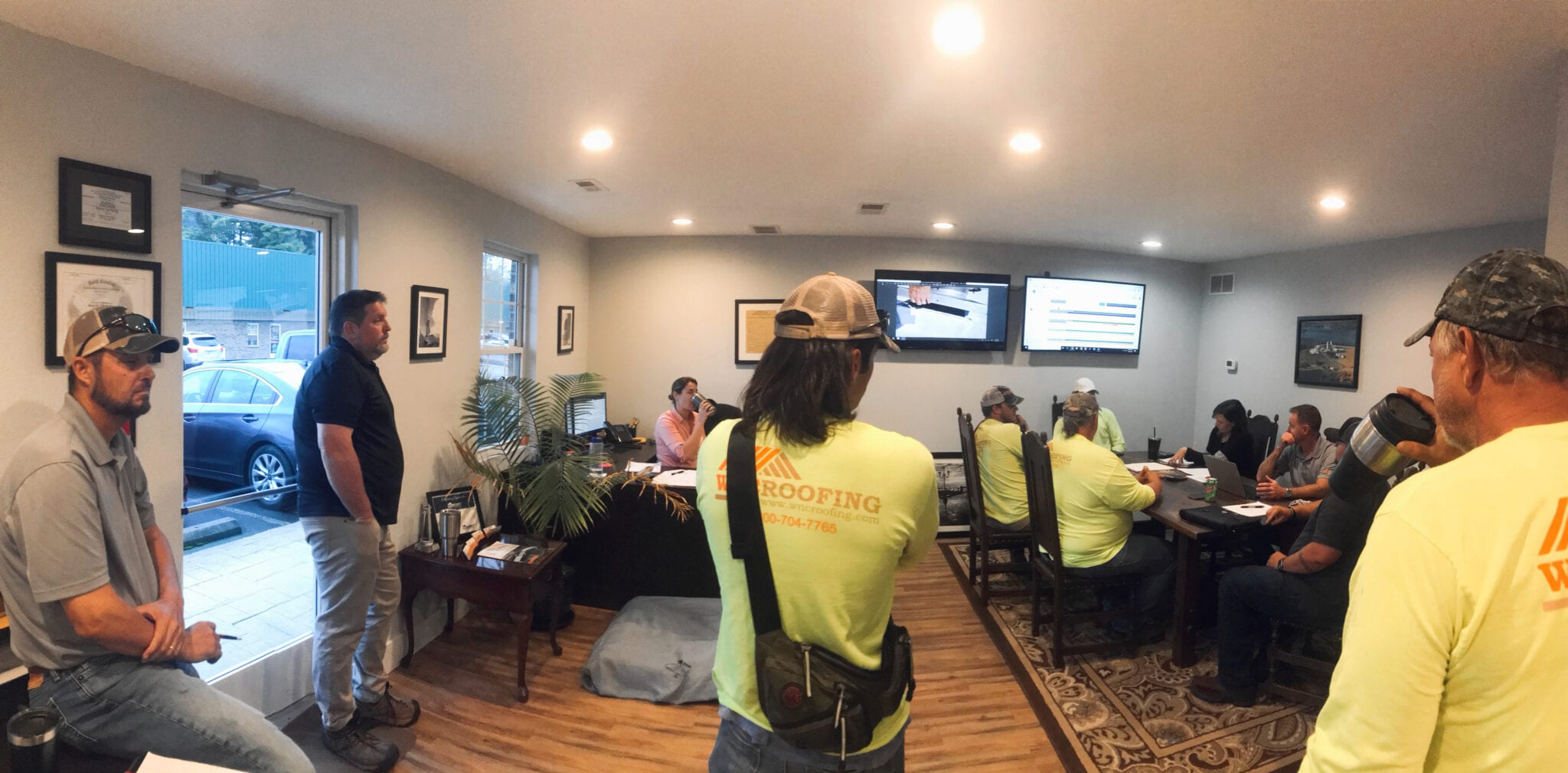 The WNC Roofing office meets in the conference room for Monday Plans