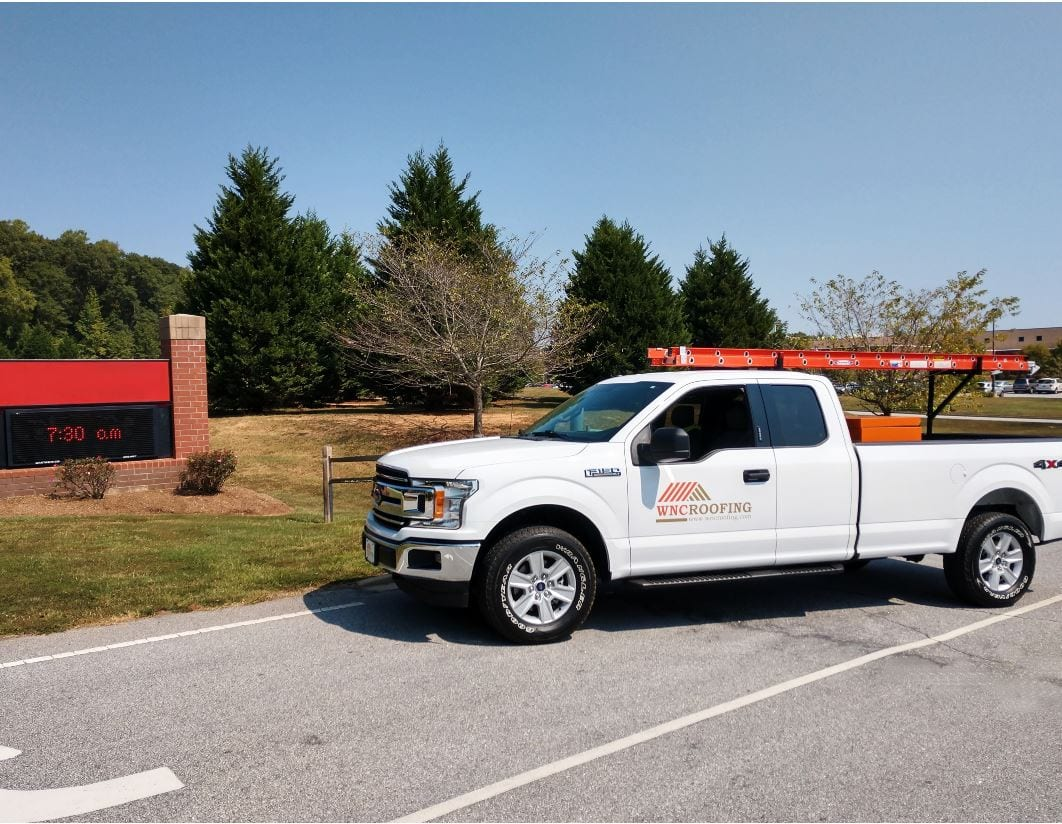 WNC Roofing Ford Truck parked in front of a Middle School in Greenville SC