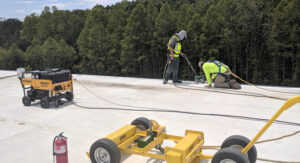 commercial roofers in greenville sc doing a repair around the edges of an industrial roof
